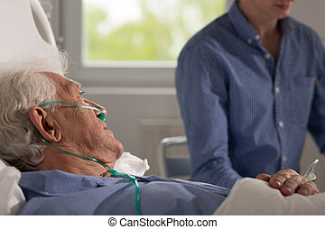 Relative visits elderly hospitalized man - View of elder...