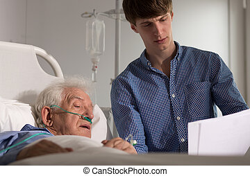 Elder patient watching his results - Picture of son reading...