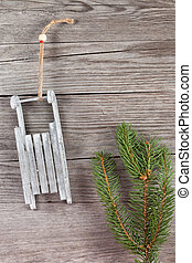 xmas greetings - fir twig and sled hanging on wooden plank