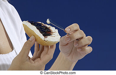 hands passing cream cheese and jam on a blue background