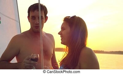 Young happy couple in love on yacht with glasses of wine at...