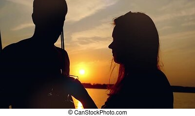Silhouette of Young happy couple in love kissing on yacht and drink wine with glasses at amazing sunset in slowmotion.
