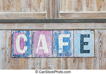 Old weathered cafe sign on distressed rustic wood wall