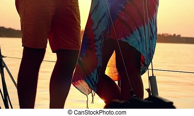 Slowmotion of young happy couple in love kissing on yacht and drink wine with glasses at amazing sunset in slowmotion.