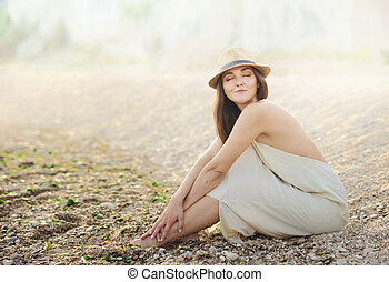 Beautiful relaxing woman sitting on a sand sea beach dressed...