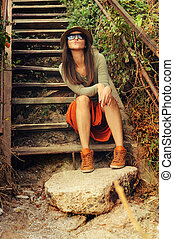 Funny young fashion girl sitting on the old wooden stairs -...