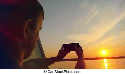 Man taking picture from his mobile phone of beautiful sunset...