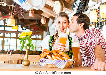 Couple drinking wheat beer in Bavarian restaurant