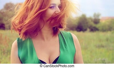 Happy smiling red-haired woman  in green long dress turns and lays down on a flower meadow. relaxing on grass
