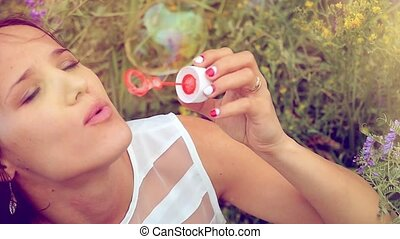 Romantic beautiful young smiles woman blowing soap balloons...