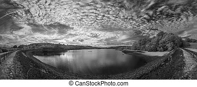 Panorama landscape in infrared of lake in English countryside in Summer with surreal colors