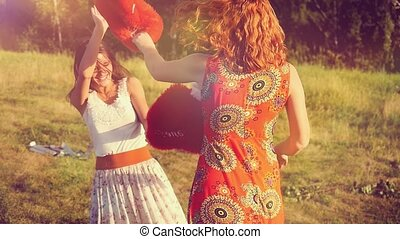 Two beautiful girl friends pillow fight on nature in sunset...