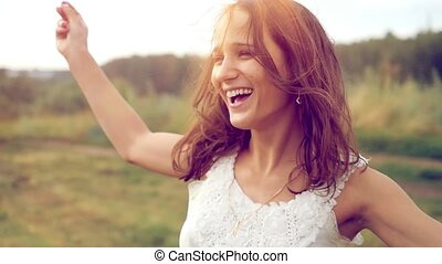 Happiness young beautiful brunette woman raises her arms...