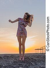 Beautiful young woman beach at sunset