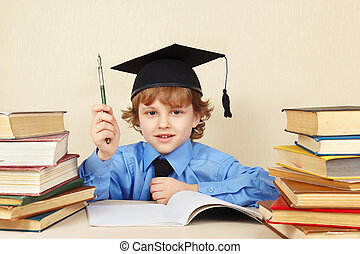 Little boy in academic hat with rarity pen among old books -...