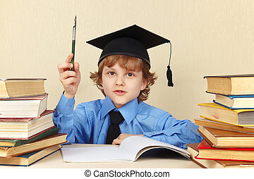 Young boy in academic hat with rarity pen among old books -...