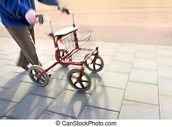 senior citizen with walking frame on sidewalk in blurred...