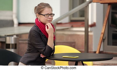 woman in a red scarf sitting in a cafe with smartphone on...