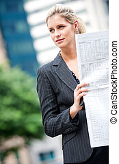 Woman with Newspapers - A young and attractive woman reading...