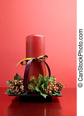 Red candle with holly and pine cone Christmas table...