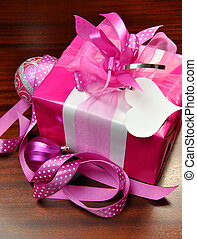 Close-up of hot candy pink Christmas present with ribbons, white gift tag and bauble decorations on a dark oak wood table.