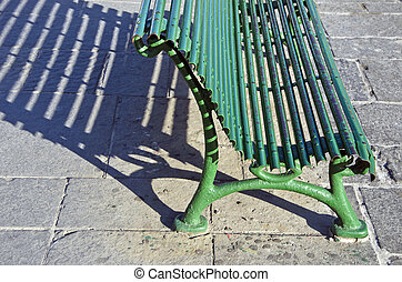 Sunlit green metal bench casting a shadow