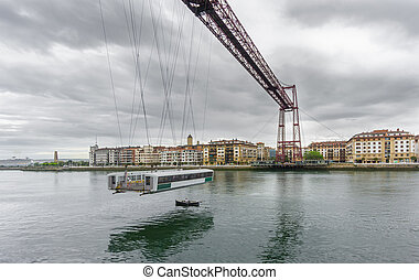 Wide angle view of the Bizkaia suspension bridge with boat -...