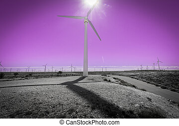 Wind turbine against sun, windmill farm and pink sky -...