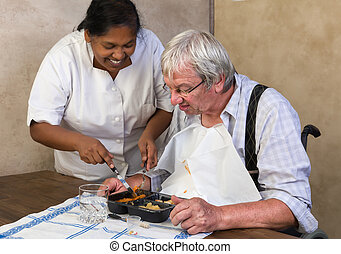 Pensioner eating - Nurse in old people's home trying to make...