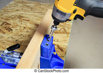 Drilling pocket hole in wood board - Drilling a pocket hole...