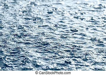 drops of heavy rain on water surface - raindrops and rippled...