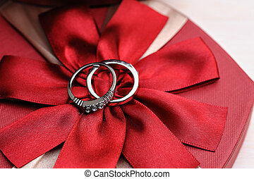 two wedding rings on a red background