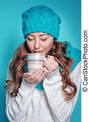 young woman in knit scarf and hat drinking hot tea