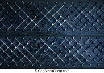 Texture of dark wooden gate with metal strips chipped