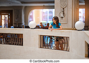 Beautiful woman leaned against the stone railing and looks...