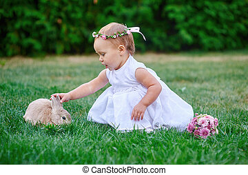 Little girl playing with a rabbit on the grass
