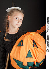 Girl in halloween costume with pumpkin on black background -...