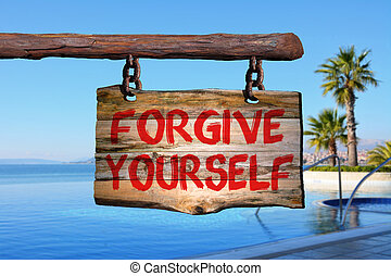 Forgive yourself sign on old wood with a blurred sea scape...