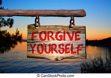Forgive yourself sign on old wood with a blurred sunset sky...
