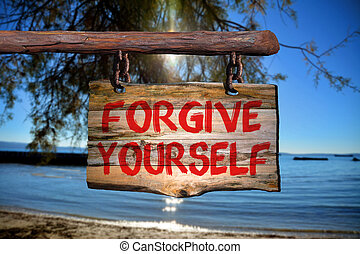 Forgive yourself sign on old wood with a blurred beach on...