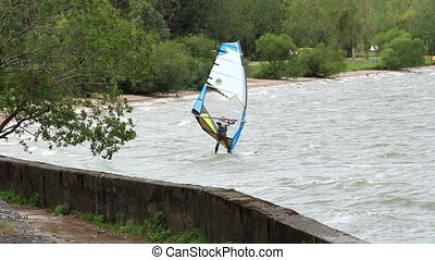 Windsurfing on the board with a sail in the lake