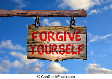 Forgive yourself sign on old wood with a blurred sky on...