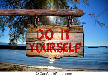 Do it yourself sign on old wood with a blurred beach on...