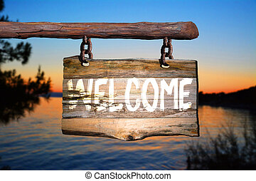 Welcome sign on old wood with a blurred sunset on background