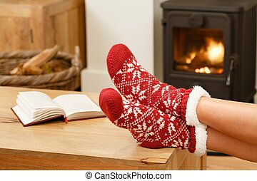 Woman relaxing in front of fire - Woman in Christmas socks...