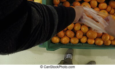 man chooses buying tangerines mandarins at the store the...