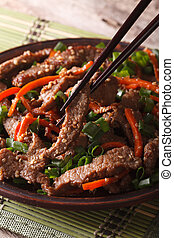 Korean bulgogi beef with carrot and onion on a plate macro. vertical