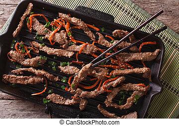 Korean bulgogi beef with carrot on grill pan closeup. horizontal top view