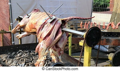 Veal carcass roasting on a rotating spit, with charcoal and...
