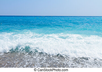 cote dAzur, France - stone beach and turquiose water splash...